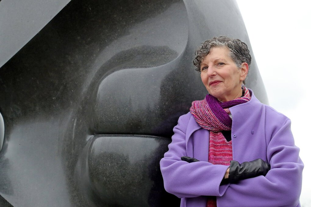 """Marcie Sillman, who has covered arts and culture in Seattle for decades, is retiring from KUOW after 35 years at the station. She's photographed here in front of Isamu Noguchi's """"Black Sun"""" sculpture at Volunteer Park. (Greg Gilbert / The Seattle Times)"""