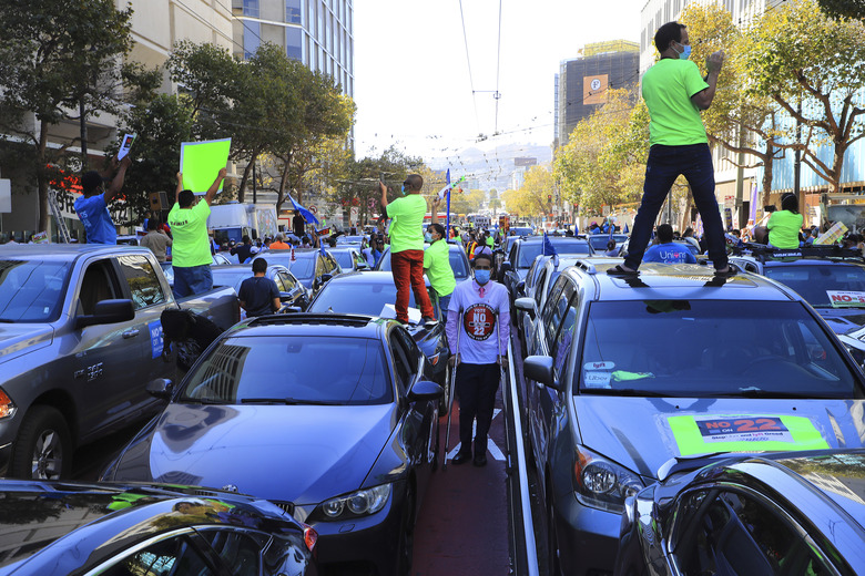 People gather outside Uber's headquarters to urge voters to reject California's Proposition 22 in San Francisco, Oct. 15, 2020. After the measure won, Uber and Lyft executives indicated that they would seek to replicate their political gains elsewhere. (Jim Wilson/The New York Times)
