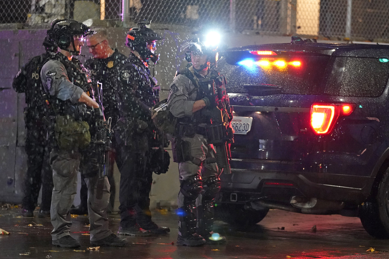 Seattle Police officers stand by with crowd-control and other weapons in the rain in front of the SPD East Precinct building, Wednesday, Nov. 4, 2020, as protesters clashed with police in Seattle. (AP Photo / Ted S. Warren)