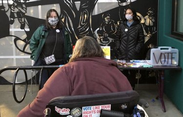 A formerly homeless woman named Rosemarie, who didn't want her last name published, visits a table staffed by volunteer Patricia Palmer and Saleena Salongo, advocacy coordinator for the Seattle-King County Coalition on Homelessness.