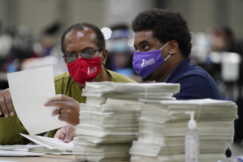 Officials sort ballots during an audit at the Georgia World Congress Center on Saturday, Nov. 14, 2020, in Atlanta. Election officials in Georgia's 159 counties are undertaking a hand tally of the presidential race that stems from an audit required by state law. (AP Photo/Brynn Anderson)