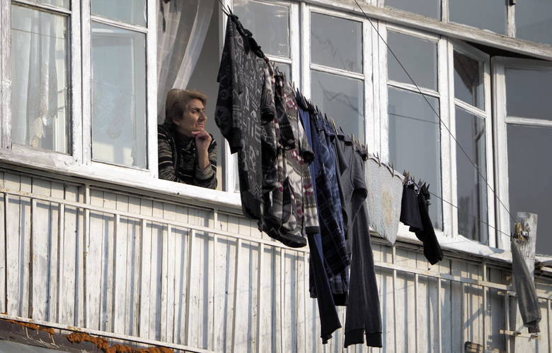 A woman looks through the window of her apartment in Stepanakert, the separatist region of Nagorno-Karabakh, Tuesday, Nov. 3, 2020. Fighting over the separatist territory of Nagorno-Karabakh entered sixth week on Sunday, with Armenian and Azerbaijani forces blaming each other for new attacks. (AP Photo)