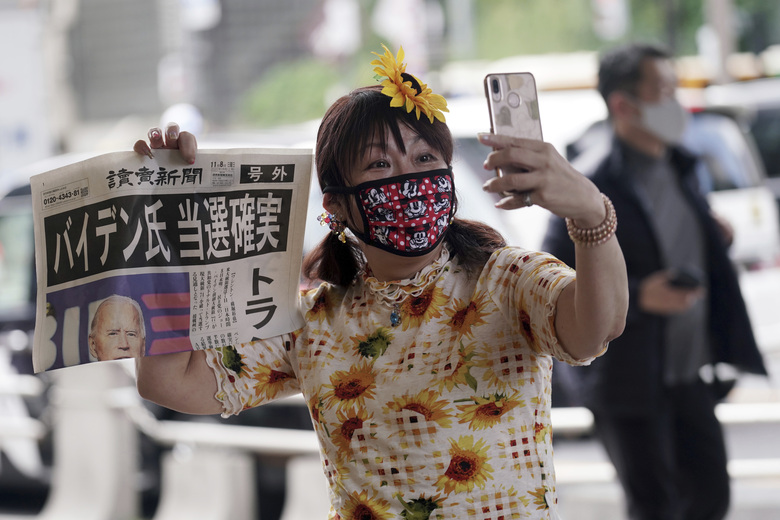 "A passer-by takes a selfie with an extra newspaper reporting on President-elect Joe Biden's win in the U.S. presidential election, in Tokyo Sunday, Nov. 8, 2020. The headline reads: ""Mr. Biden Assured to win.""(AP Photo/Eugene Hoshiko)"
