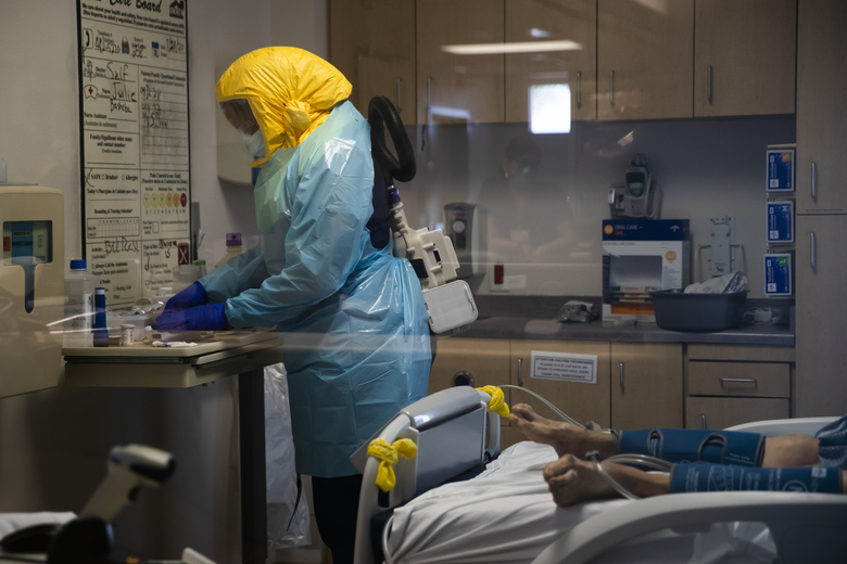FILE – In this July 21, 2020, file photo, a nurse assists a COVID-19 patient at El Centro Regional Medical Center in El Centro, Calif. In November 2020, California is reaching an unwelcome coronavirus record: its 1 millionth positive test. (AP Photo/Jae C. Hong, File)