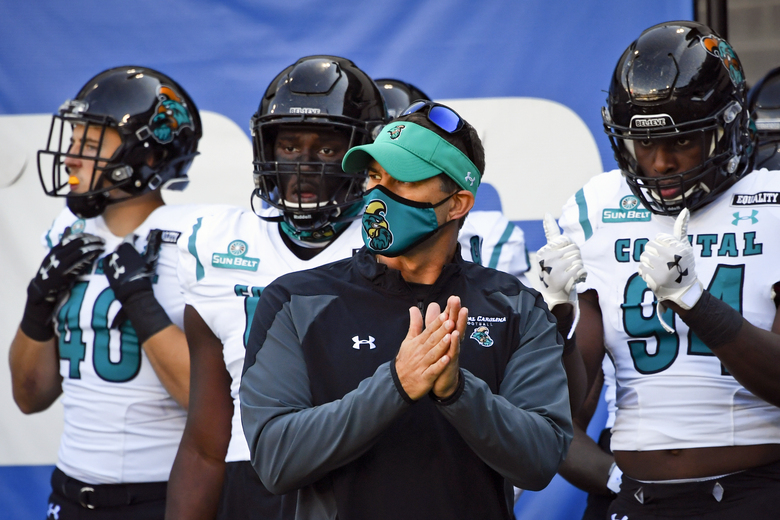 FILE – In this Saturday, Oct. 31, 2020, file photo, Coastal Carolina head coach Jamey Chadwell waits to lead his team onto the field before an NCAA football game against Georgia State in Atlanta. An unusual college football season has produced some unexpected unbeaten teams dotting the AP Top 25 with about a month left. Led by No. 7  Cincinnati and No. 8 BYU, five teams from outside the Power Five conferences have yet to lose. (AP Photo/John Amis, File)