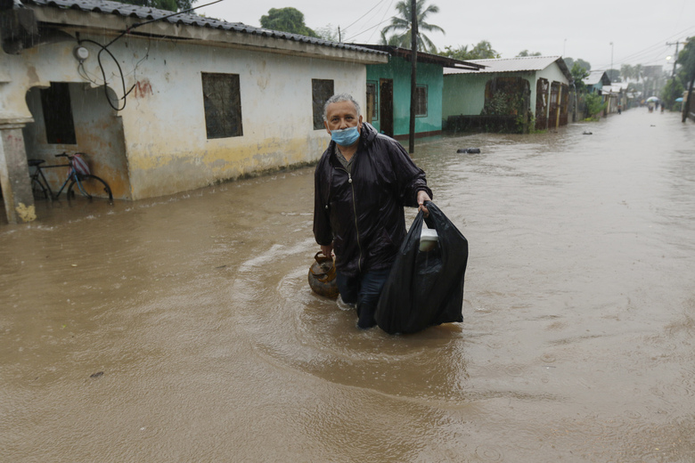 A man walks in knee-deep floodwaters carrying belongings in San Manuel, Honduras, Wednesday, Nov. 4, 2020. Eta weakened from the Category 4 hurricane to a tropical storm after lashing the Caribbean coast for much of Tuesday, its floodwaters isolating already remote communities and setting off deadly landslides. (AP Photo/Delmer Martinez)