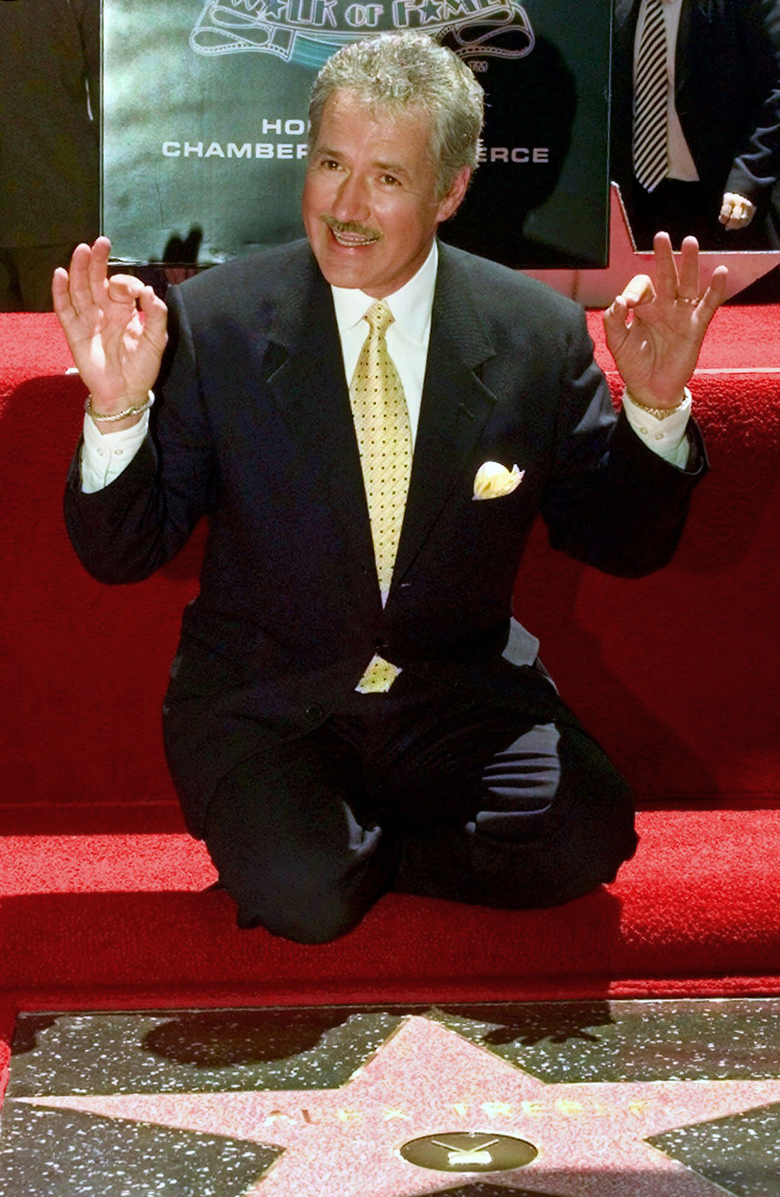 "FILE – In this May 17, 1999, file photo, Emmy award-winning game show host Alex Trebek celebrates his newly-dedicated star on the Hollywood Walk of Fame in Los Angeles. Jeopardy!"" host Alex Trebek died Sunday, Nov. 8, 2020, after battling pancreatic cancer for nearly two years. Trebek died at home with family and friends surrounding him, ""Jeopardy!"" studio Sony said in a statement. Trebek presided over the beloved quiz show for more than 30 years. (AP Photo/Nick Ut, File)"
