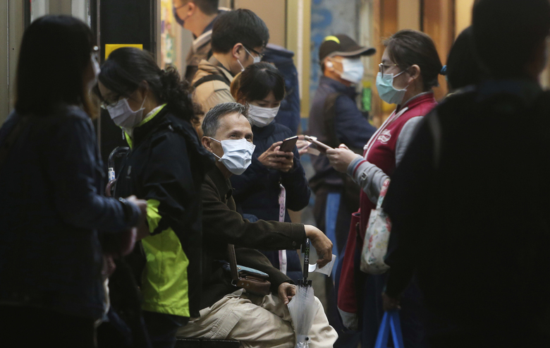 People wear face masks to help curb the spread of the coronavirus in a public area of Taipei, Taiwan, Monday, Nov. 30, 2020. (AP Photo/Chiang Ying-ying)
