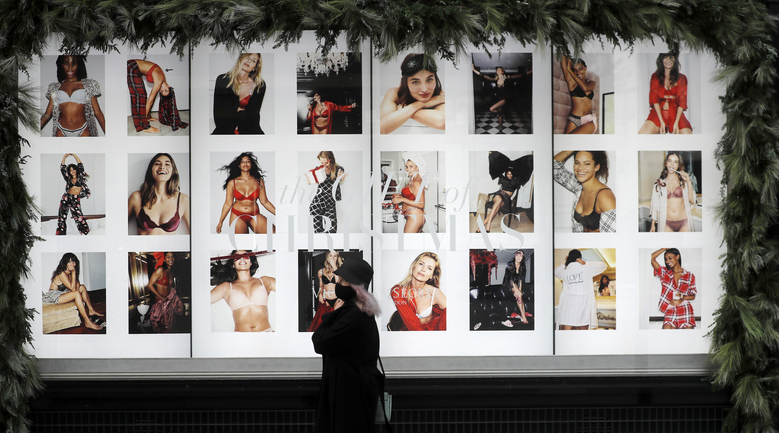 A woman wearing a face covering walks past an advertising window of a closed shop in London, Friday, Nov. 6, 2020. Britain's lockdown started Thursday, shuttering restaurants, hairdressers and clothing stores until at least Dec. 2. (AP Photo/Frank Augstein)