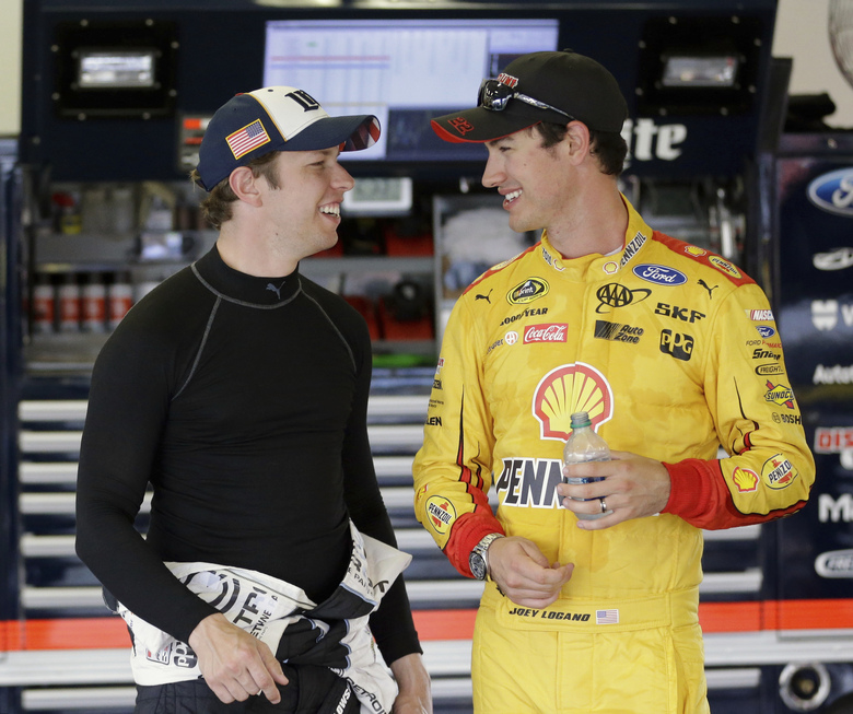 FILE- In this June 30, 2016, file photo, Brad Keselowski, left, and Joey Logano talk in their garage during NASCAR Sprint Cup auto racing practice at Daytona International Speedway in Daytona Beach, Fla. Denny Hamlin will be racing for the Cup against Team Penske drivers Joey Logano and Brad Keselowski, as well as Chase Elliott of Hendrick Motorsports. (AP Photo/John Raoux, File)