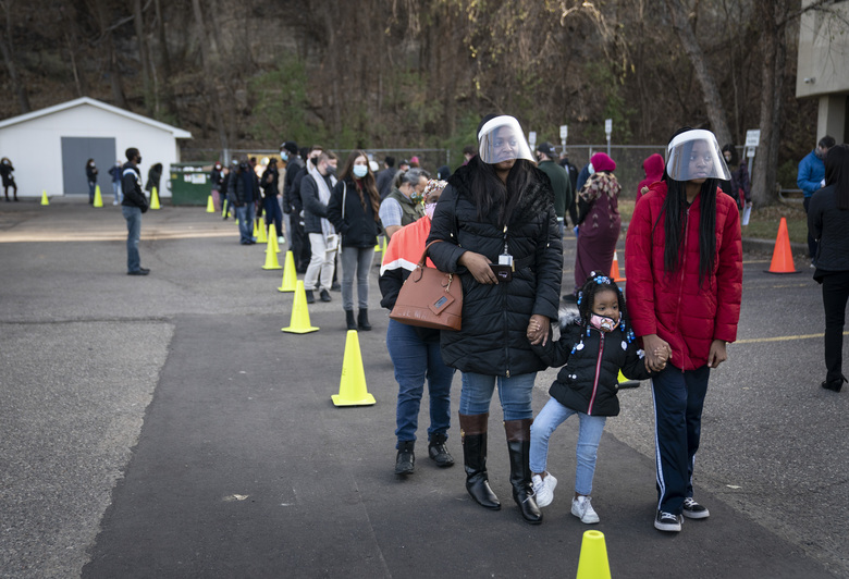 Natasha DaVis and her daughters Natavia DaVis, middle, and Natasia DaVis waited in a large line to early vote, some up to two hours, at the Ramsey County Elections office in St. Paul, Minn., on Monday, Nov. 2, 2020. (Renee Jones Schneider/Star Tribune via AP)