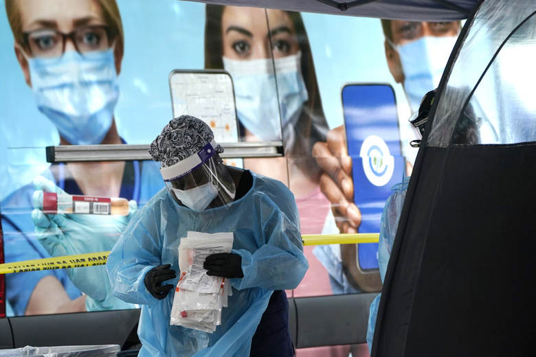 A health care employee works at a walk-up COVID-19 testing site, Wednesday, Nov. 18, 2020, in Miami. The number of people hospitalized with COVID-19 in the U.S. has doubled in the past month and set new records every day this week. (AP Photo/Lynne Sladky)