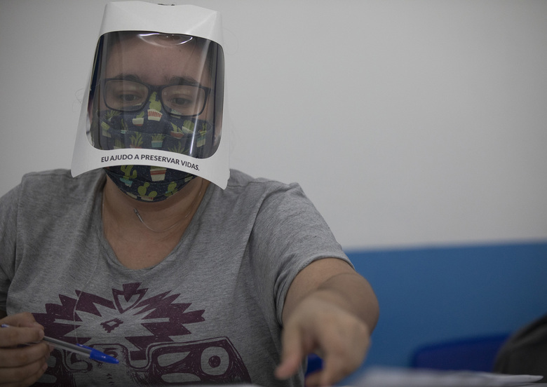 "An electoral worker wears a face shield with a sign that reads ""I help to preserve lives"" during municipal elections at a polling station in the Rocinha slum in Rio de Janeiro, Brazil, Sunday, Nov. 15, 2020.  (AP Photo/Silvia Izquierdo)"