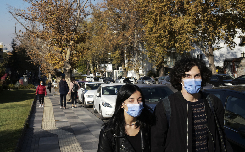 People wearing masks to help protect against the spread of coronavirus, walk along a public garden, in Ankara, Turkey, Friday, Nov. 13, 2020. Turkey's interior ministry has banned smoking in public places, including parks, across the country to curb the spread of COVID-19. (AP Photo/Burhan Ozbilici)