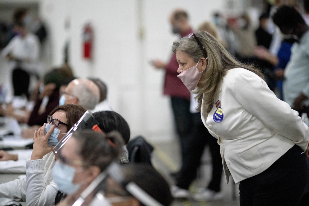 A Republican election challenger, at right, watches over election inspectors as they examine a ballot as votes are counted into the early morning hours Wednesday, Nov. 4, 2020, at the central counting board in Detroit. (AP Photo/David Goldman)