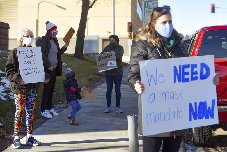 Demonstrators hold signs demanding a mask mandate from the city council on Monday, Nov. 16, 2020 outside Carnegie Town Hall in Sioux Falls, S.D. (Erin Bormett/The Argus Leader via AP)