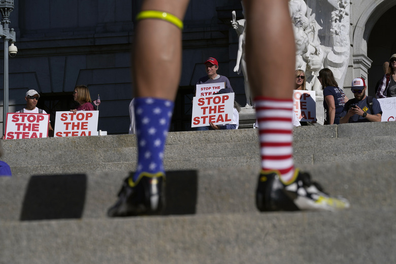 A supporter of President Donald Trump wears red, white and blue socks as he speaks with demonstrators, rear, outside the Pennsylvania State Capitol, Friday, Nov. 6, 2020, in Harrisburg, Pa., as vote counting continues following Tuesday's election. (AP Photo/Julio Cortez)