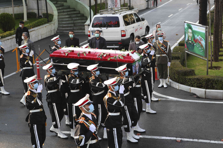 """In this photo released by the official website of the Iranian Defense Ministry, military personnel carry the flag draped coffin of Mohsen Fakhrizadeh, a scientist who was killed on Friday, in a funeral ceremony in Tehran, Iran, Monday, Nov. 30, 2020. Iran held a funeral service Monday for the slain scientist who founded its military nuclear program two decades ago, with the Islamic Republic's defense minister vowing to continue the man's work """"with more speed and more power."""" (Iranian Defense Ministry via AP)"""