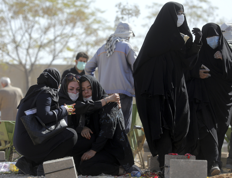 Mourners attend the funeral of a person who died from COVID-19 at the Behesht-e-Zahra cemetery just outside Tehran, Iran, Sunday, Nov. 1, 2020. The cemetery is struggling to keep up with the coronavirus pandemic ravaging Iran, with double the usual number of bodies arriving each day and grave diggers excavating thousands of new plots. (AP Photo/Ebrahim Noroozi)