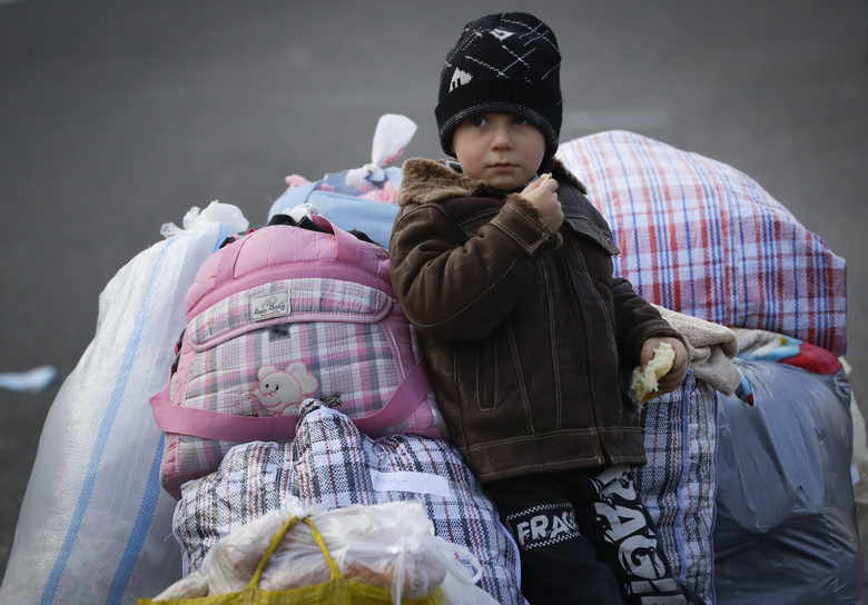 An ethnic Armenian boy eats bread as he and many other refugees return to Stepanakert, the capital of the separatist region of Nagorno-Karabakh, on Tuesday, Nov. 17, 2020. Russian peacekeepers have started to move into the region, a total of 1,960 of them are to be sent in under a five-year mandate. Russia's Defense Ministry reported that the peacekeepers accompanied about 1,200 people returning to Nagorno-Karabakh from Armenia since Saturday. (AP Photo/Sergei Grits)