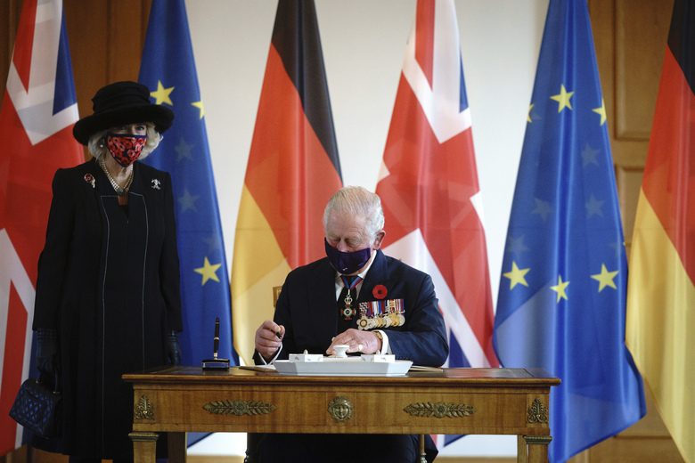 Prince Charles and his wife Camilla sign the guest book before a conversation at Bellevue Palace in Berlin, Sunday, Nov.15, 2020. The Prince of Wales and the Duchess of Cornwall are in Berlin on the occasion of the central commemoration of the Volkstrauertag. This year's national day of mourning in memory of the victims of National Socialism and the dead of both world wars is dedicated to German-British friendship. (Kay Nietfeld/dpa via AP)