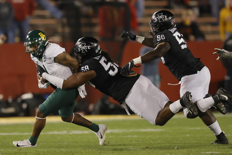 Baylor running back Trestan Ebner, left, carries the ball as Iowa State defensive end Eyioma Uwazurike, center, dives for the tackle while defensive lineman Latrell Bankston, right, trails during the first half of an NCAA college football game, Saturday, Nov. 7, 2020, in Ames, Iowa. (AP Photo/Matthew Putney)