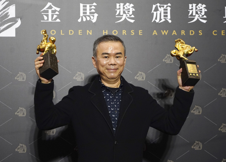"Taiwanese director Chen Yu-hsun holds his awards for Best Director and Best Original Screenplay at the 57th Golden Horse Awards in Taipei, Taiwan, Saturday, Nov. 21, 2020. Chen won for the film ""My Missing Valentine"" at this year's Golden Horse Awards – one of the Chinese-language film industry's biggest annual events. (AP Photo/Billy Dai)"