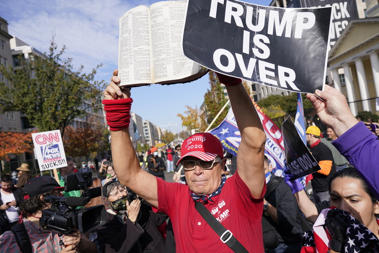 A supporter of President Donald Trump holds a Bible as people gather on a section of 16th Street renamed Black Lives Matter Plaza, Friday Nov. 13, 2020, in Washington. (AP Photo/Jacquelyn Martin)