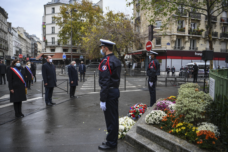 Paris Mayor Anne Hidalgo, left, and French Prime Minister Jean Castex, 2nd left, participate in a wreath laying ceremony, marking the 5th anniversary of the Nov. 13, 2015 attacks outside the Bonne Biere cafe bar in Paris, Friday, Nov. 13, 2020. In silence and mourning, France is marking five years since 130 people were killed by Islamic State extremists who targeted the Bataclan concert hall, Paris cafes and the national stadium. (Christophe Archambault/Pool Photo via AP)
