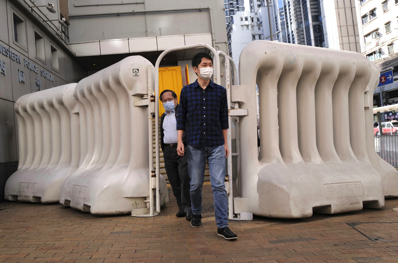 Pro-democracy legislator Ted Hui, right, and his lawyer, Albert Ho, rear, leave a police station after ho was released in Hong Kong Wednesday, Nov. 18, 2020. Hong Kong police arrested three former opposition lawmakers, Hui, Eddie Chu and Ray Chan, for disrupting legislative meetings several months ago, as concerns grow over a crackdown on the city's pro-democracy camp. (AP Photo/Vincent Yu)