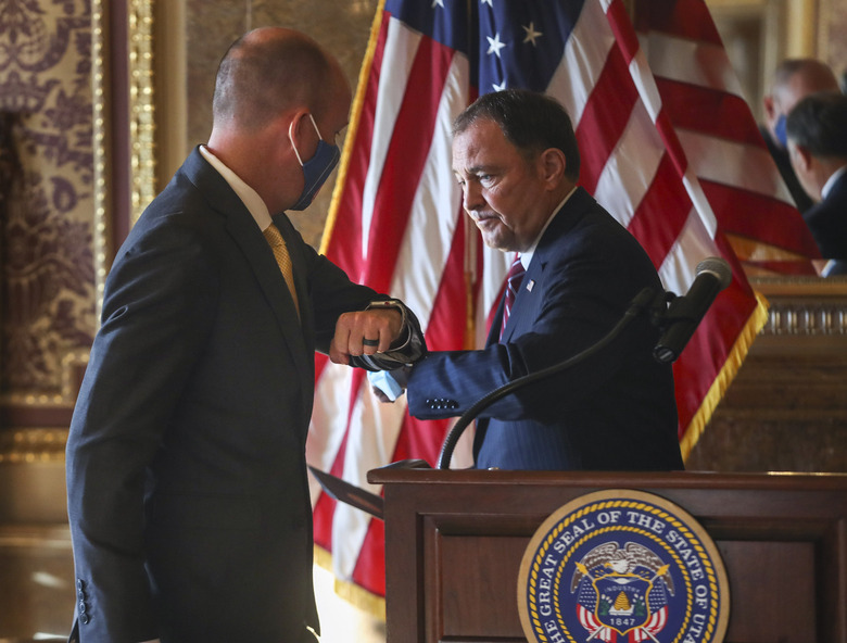 Gov. Gary Herbert, right, and Gov.-elect Spencer Cox exchange elbows during a press conference announcing details related to their upcoming transition of leadership at the Utah State Capitol on Thursday, Nov. 5, 2020, in Salt Lake City. Cox, who won the governor's race this week, said he is prepared to continue the fight against COVID-19 when he succeeds Herbert in January. He said he hopes to focus on ramping up testing, adding more contact tracers and implementing vaccine distribution. (Steve Griffin/Deseret News, via AP, Pool)