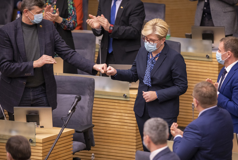 Members of Lithuania's parliament applaud Lithuania's Homeland Union and Lithuanian Christian Democrats party leader Ingrida Simonyte, center, at the parliament in Vilnius, Lithuania, Tuesday, Nov. 24, 2020. Lithuania's parliament approved Ingrida Simonyte as the new prime minister on Tuesday. (AP Photo/Mindaugas Kulbis)