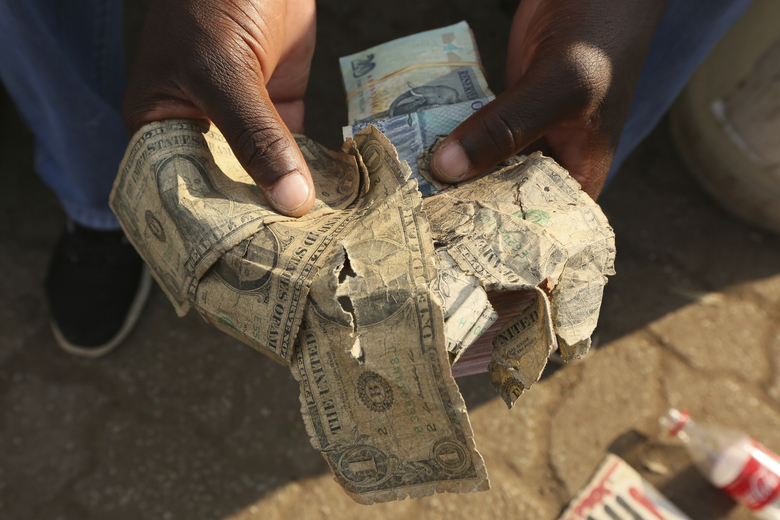 Albert Marombe shows grimmy, tattered $1 bills at a busy market in Harare, in this Wednesday, Oct, 21, 2020 photo.  Worn out or shredded by rats, one dollar notes are king in Zimbabwe, beset by a continuing economic crisis, and enterprising traders are repairing old notes for desperate customers.( AP Photo/Tsvangirayi Mukwazhi)