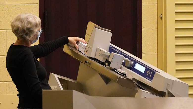 A worker scans mail-in ballots through a counting machine before they are counted, Wednesday, Nov. 4, 2020, at the convention center in Lancaster, Pa., following Tuesday's election. (AP Photo/Julio Cortez)