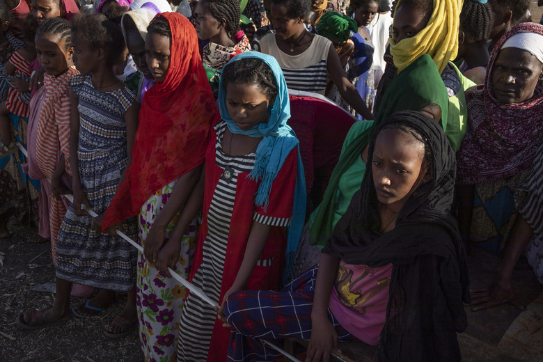 """Tigray women who fled the conflict in the Ethiopia's Tigray region, wait to receive aid at Village 8, the transit centre near the Lugdi border crossing, eastern Sudan, Sunday, Nov. 22, 2020. Ethiopia's military is warning civilians in the besieged Tigray regional capital that there will be """"no mercy"""" if they don't """"save themselves"""" before a final offensive to flush out defiant regional leaders, a threat that Human Rights Watch on Sunday said could violate international law. (AP Photo/Nariman El-Mofty)"""