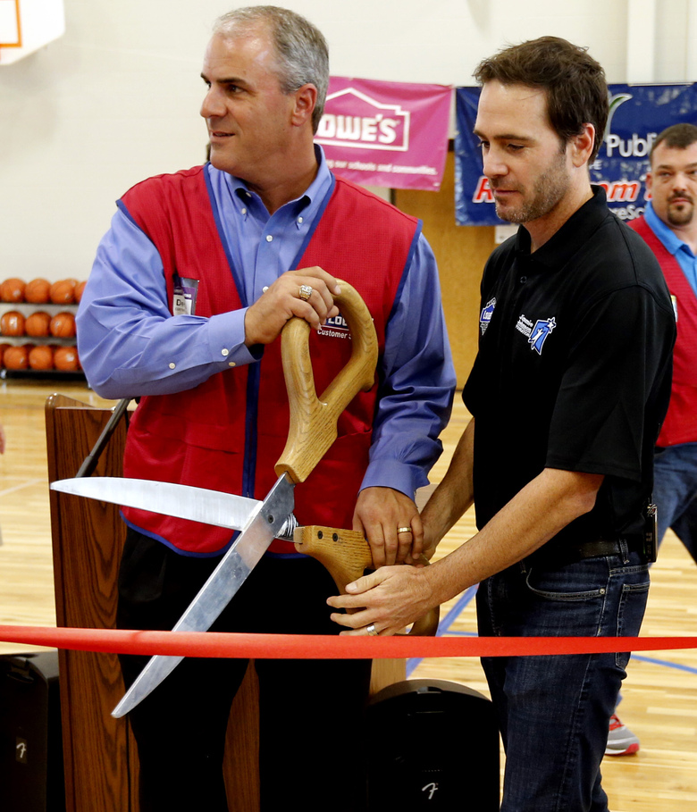 FILE  – This Thursday, Oct. 2, 2014, file photo shows Dennis Knowles, left, executive director of U.S. stores for Lowe's, NASCAR driver Jimmie Johnson participate in a ribbon-cutting ceremony at Highland East Junior High to celebrate the opening of three area school gyms, in Moore, Okla. Johnson and Lowe's were major contributors to rebuilding facilities after a 2013 tornado destroyed homes, business, and schools in Moore. NASCAR's nicest guy will run his final race this week and close a remarkable career. Jimmie Johnson's record-tying seven Cup titles are well celebrated, but his charitable work goes less noticed. The Jimmie Johnson Foundation has donated more than $12 million to schools and programs since it launched. (Steve Sisney/The Oklahoman via AP, File)