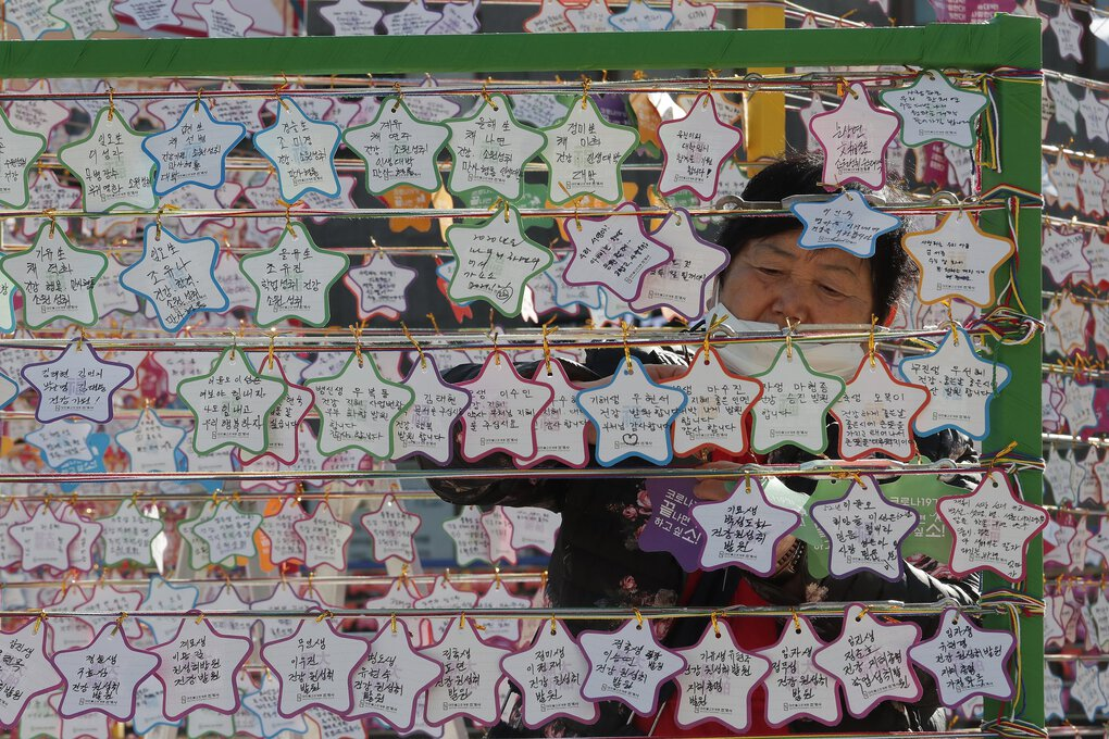 A woman hangs on a paper note to wish for her child's success in the college entrance exams at the Jogyesa Buddhist temple in Seoul, South Korea, on Thursday. Hundreds of thousands of masked students in South Korea took the highly competitive university entrance exam Thursday despite a viral resurgence. (Ahn Young-joon / The Associated Press)