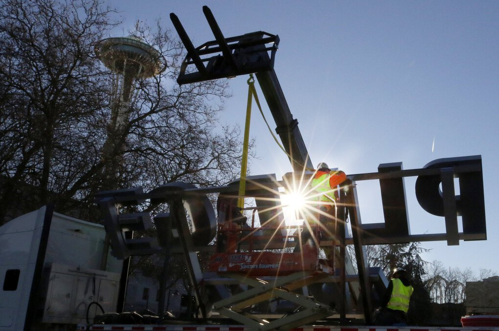 Straps are secured to the Climate Pledge Arena signage so it can be off-loaded at Seattle Center Wednesday. Installation is expected of the four-sided signage on Saturday at the former KeyArena. (Alan Berner / The Seattle Times)