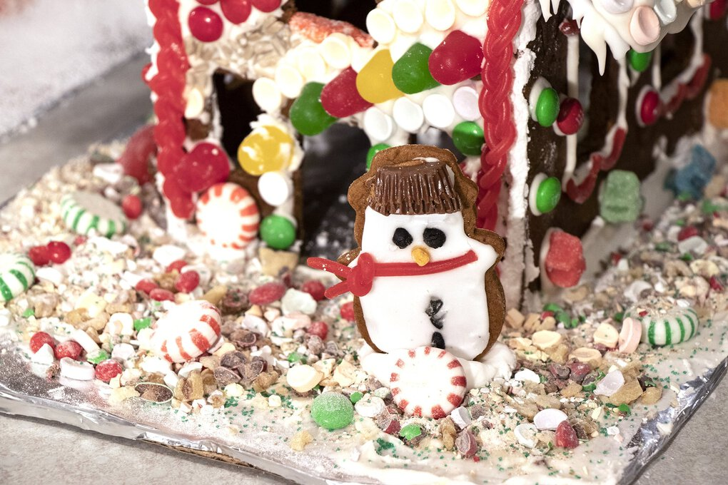 A snowman shaped gingerbread cookie hangs out on our lawn of crushed hard candies, peppermints and green sugar. (Stephanie Hays / The Seattle Times)