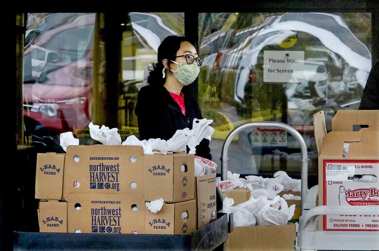 Volunteer Elaine Liu waits  with boxed meals for delivery at the entrance of the Asian Counseling and Referral Service in Seattle. The ACRS is one of the agencies aided by The Seattle Times Fund For The Needy. (Alan Berner / The Seattle Times)