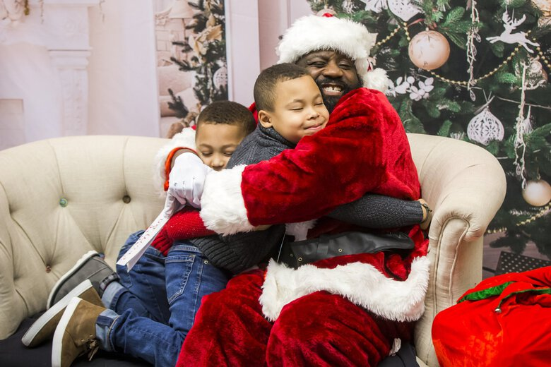 Ian Hunter, 5, left, and his brother Logan Hunter, 7, give a big hug to Santa after getting their photo taken together during a different Black Santa at the Northwest African American Museum in 2018. (Bettina Hansen / The Seattle Times)