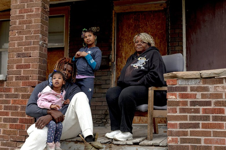Lisa Thompson sits with her son and his two daughters at her former home in Toledo, Ohio, in October. Thompson's appliances were stolen while a roof was being put on her home. An adjuster sent by the insurance company accused her of orchestrating the theft.(Sylvia Jarrus / The New York Times)