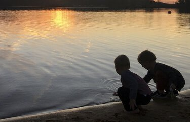 This image provided by Lucy O'Donoghue shows a children playing by a lake. Although this year's quarantine limited Lucy O'Donoghue's opportunities for travel, she found ways to focus on her two sons by taking them for 'micro-holidays' at a beach near their Georgia home. (Lucy O'Donoghue via AP) LENT104 LENT104
