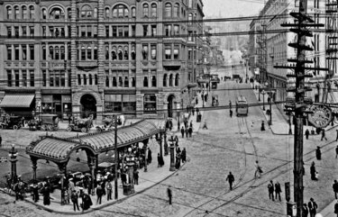 THEN: Behind the pergola, Henry Yesler's hallmark Pioneer Building (left, 1890) and the stately flat-iron Seattle Hotel (1891) straddle Yesler Way. The stairway to the park's luxurious lavatory is seen beneath the pergola at front, near First Avenue. Credit: Webster & Stevens / Paul Dorpat Collection