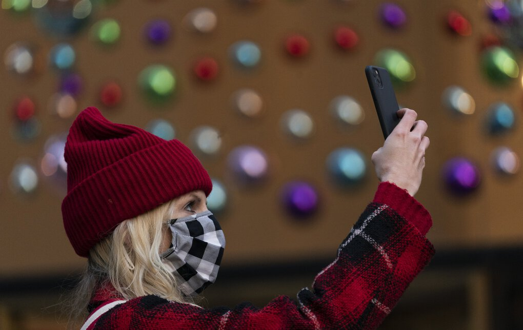 A woman photographs the Rockefeller Center Christmas Tree, Thursday, Dec. 3, 2020 in New York.  What's normally a chaotic, crowded tourist hotspot during the holiday season is instead a mask-mandated, time-limited, socially distanced locale due to the coronavirus pandemic.  (AP Photo/Mark Lennihan) NYML115 NYML115 (Mark Lennihan / The Associated Press)