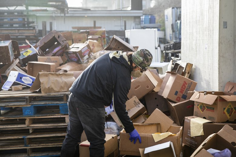 A mountain of cardboard boxes piles up outside the Rainier Valley Food Bank warehouse. Another volunteering opportunity is for breaking down boxes, said Otis Pimpleton, warehouse manager. (Bettina Hansen / The Seattle Times)