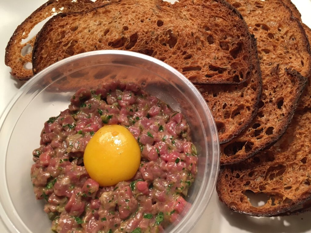 For a little turf to go with your Walrus and Carpenter surf, get the classic steak tartare with a glowing egg yolk and lacy rye-bread crackers. (Bethany Jean Clement / The Seattle Times)