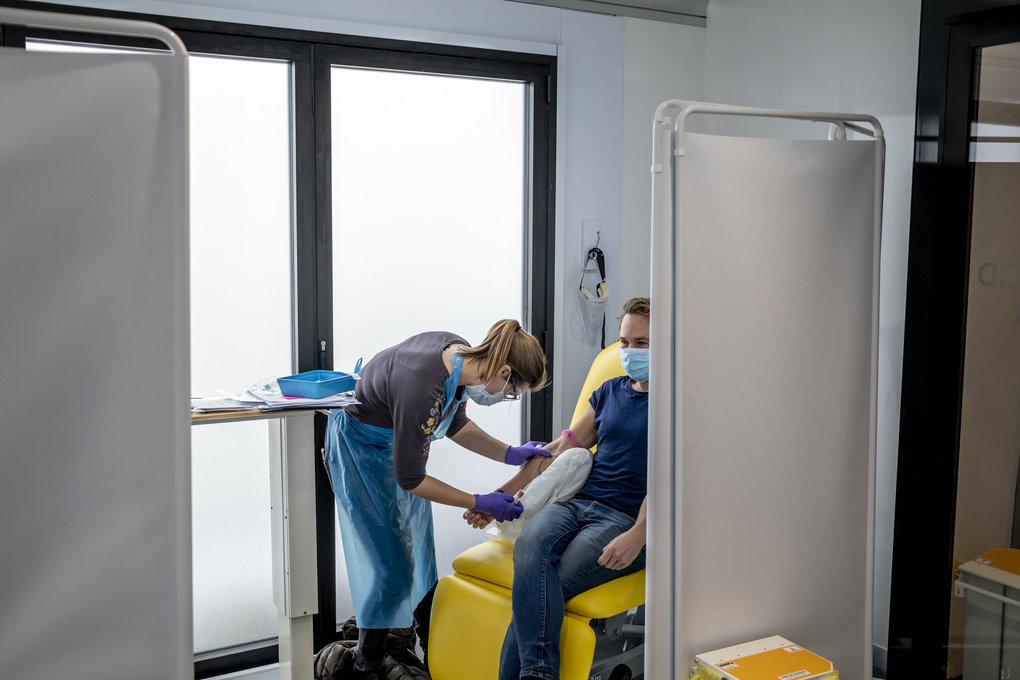 A volunteer undergoes testing in Oxford, England, as part of a vaccine trial by AstraZeneca and the University of Oxford on Nov. 19, 2020. AstraZeneca's vaccine, which is cheaper and easier to store than Pfizer's, is also being vetted for emergency approval in Britain. (Andrew Testa/The New York Times)
