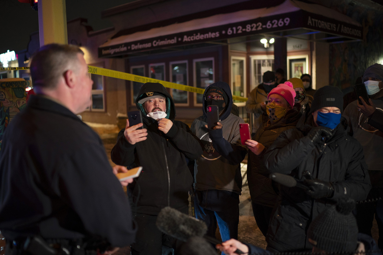 Minneapolis police spokesman John Elder brief community members and others about the officer-involved shooting Wednesday. He said the incident happened about 6:15 p.m. while officers were carrying out a traffic stop with a man suspected of a felony. A woman in the car was unhurt, Elder said. (Jeff Wheeler/Star Tribune via AP)
