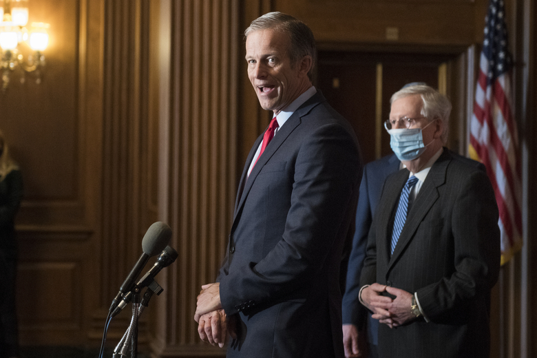 Senate Majority Leader Mitch McConnell of Ky., listens as Sen. John Thune, R-S.D., speaks during a news conference with other Senate Republicans on Capitol Hill in Washington, Tuesday, Dec. 15, 2020. (Rod Lamkey/Pool via AP)